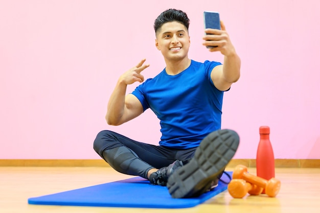 Young hispanic fitness sports man doing exercise with dumbbells doing selfie shot on mobile phone spend time in gym