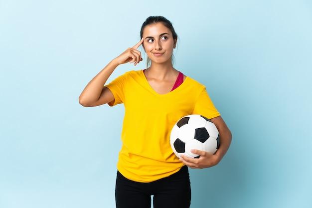 Молодой испаноязычный футболист женщина изолирована на синем фоне с сомнениями и мышлением