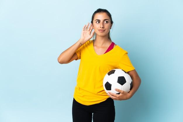 Молодая латиноамериканская женщина-футболист над изолированной на синей стене сомневается