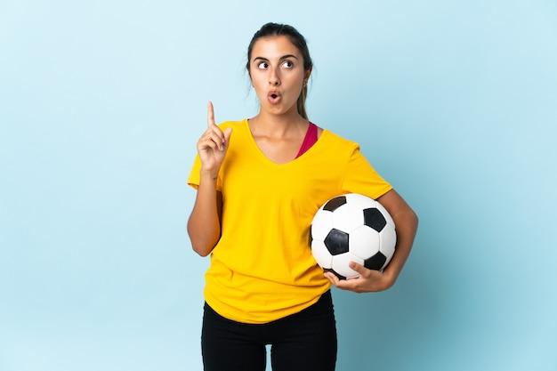 Молодая латиноамериканская женщина-футболист над изолированной на синей стене думает об идее, указывая пальцем вверх