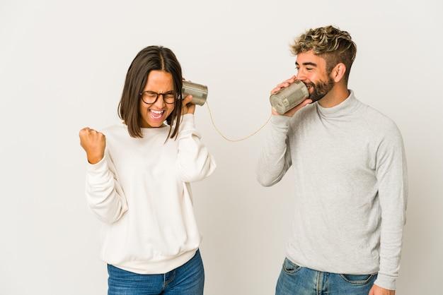 ブリキ缶システムを介して話している若いヒスパニック系の友人は、勝利、勝者の概念の後に拳を上げます。