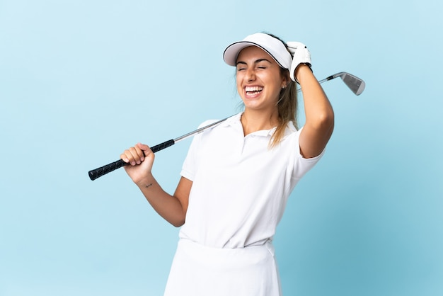 Young hispanic golfer woman over isolated blue wall smiling a lot