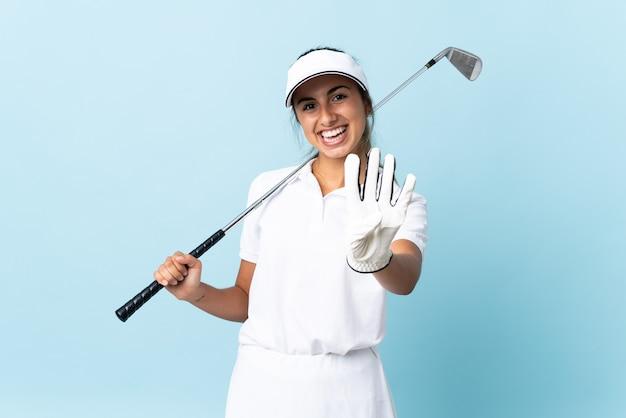 Молодая латиноамериканская гольфистка над изолированной синей стеной счастлива и считает четыре пальцами