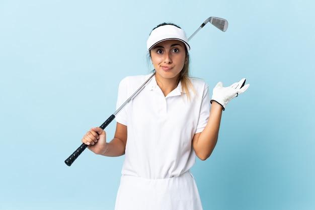 手を上げている間疑いを持っている孤立した青い壁の上の若いヒスパニックゴルファーの女性