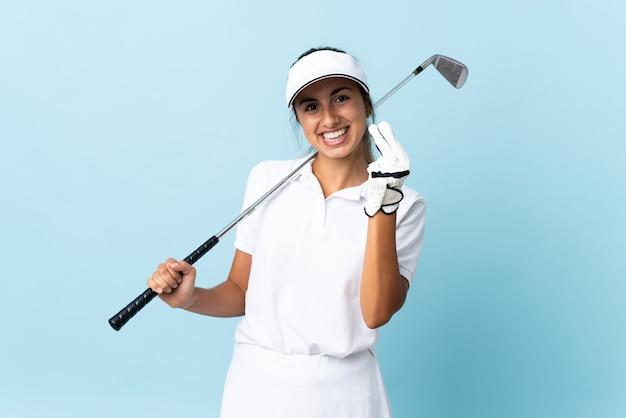 お金のジェスチャーを作る孤立した青い壁の上の若いヒスパニックゴルファーの女性