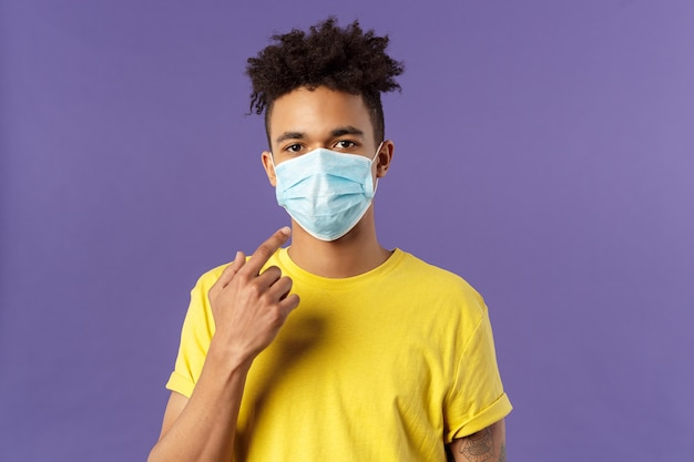 Young hispanic guy with afro haircut, wear and point at face mask, social-distancing during pandemic