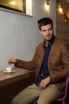 Giovane maschio ispanico in una giacca di pelle seduto al tavolo e bere caffè