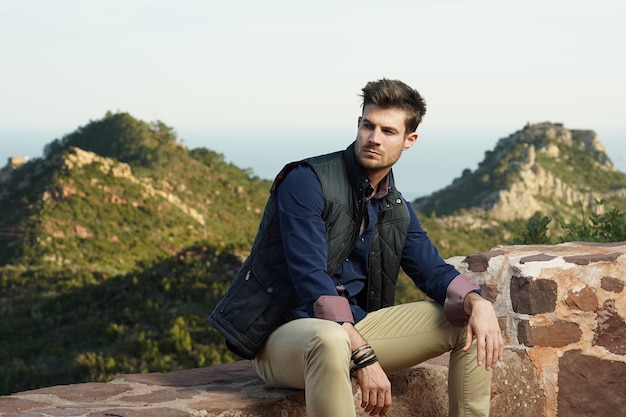 Young hispanic male model wearing a blue shirt and a black jacket posing near a stone wall