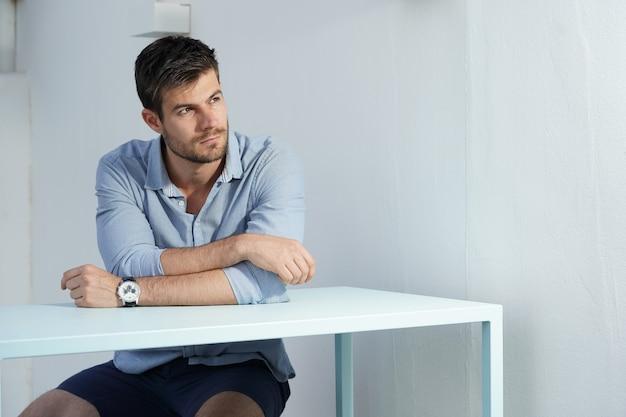 Giovane maschio ispanico che indossa una camicia blu in posa accanto a una scrivania bianca