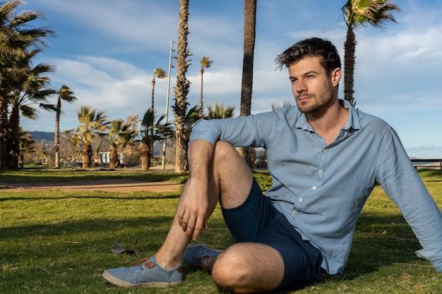 Giovane maschio ispanico che indossa una maglietta blu seduto in un parco con molte palme sullo sfondo