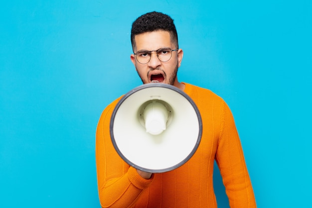 Young hispanic man angry expression and holding a megaphone