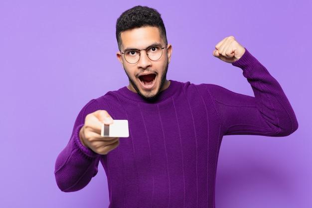 성공적인 승리를 축하하고 신용 카드를 들고 젊은 히스패닉 남자