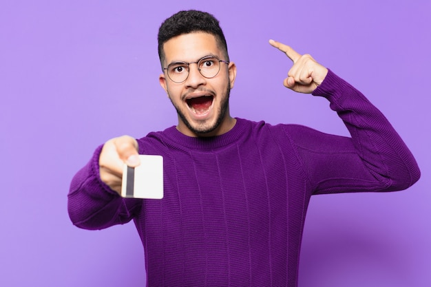 성공적인 승리를 축하하고 신용 카드를 들고 있는 젊은 히스패닉 남자
