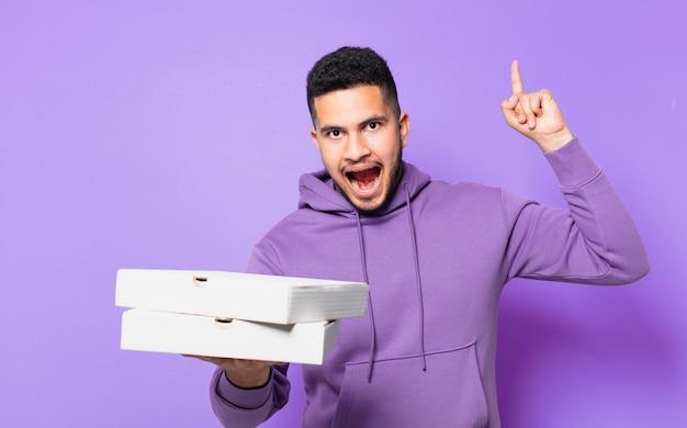 Молодой латиноамериканец празднует успешную победу и держит пиццу на вынос
