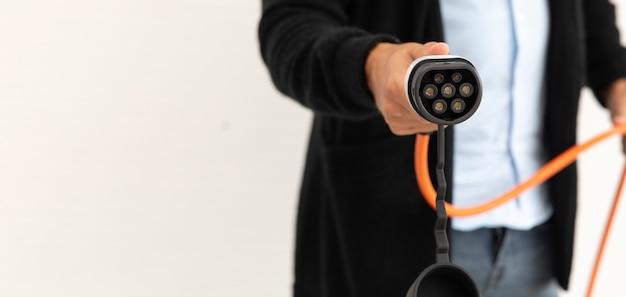 Молодой латиноамериканец заряжает электромобиль от штепсельной вилки электромобиля. рука человека, держащего вилку, изолированную на белом фоне.