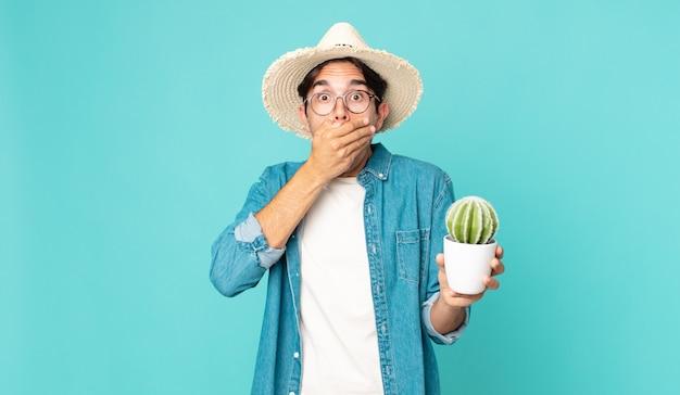 ショックを受けてサボテンを持って手で口を覆う若いヒスパニック系男性