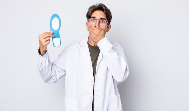 ショックを受けた手で口を覆っている若いヒスパニック系の男性。足病専門医の概念