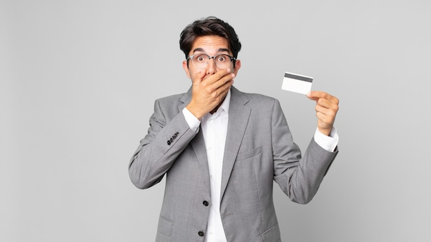 Young hispanic man covering mouth with hands with a shocked and holding a credit card