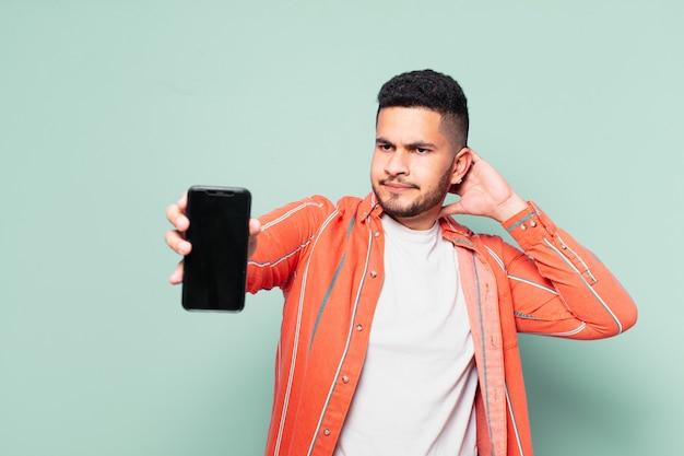 Молодой латиноамериканец сомневается или неуверенно выражает свое мнение и держит мобильный телефон