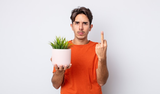 Young hispanic man feeling angry, annoyed, rebellious and aggressive. decorative plant concept