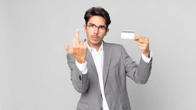 Young hispanic man feeling angry, annoyed, rebellious and aggressive and holding a credit card