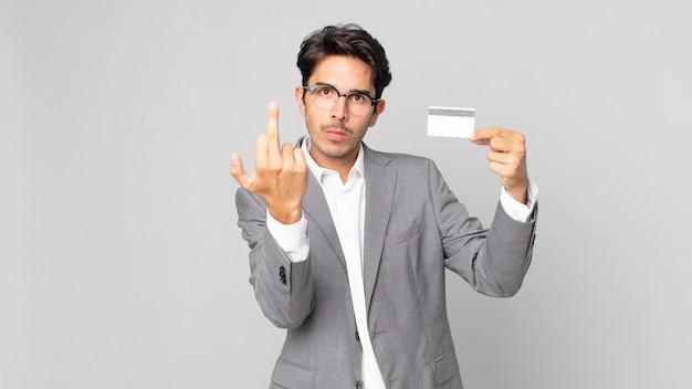 젊은 히스패닉 남자는 화가 나고 짜증이 나고 반항적이고 공격적이며 신용 카드를 들고 있습니다.