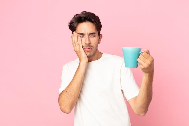 疲れてコーヒーマグを持った後、退屈、欲求不満、眠い感じの若いヒスパニック系男性