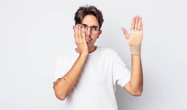 疲れた後、退屈、欲求不満、眠い感じの若いヒスパニック系男性。手の包帯の概念