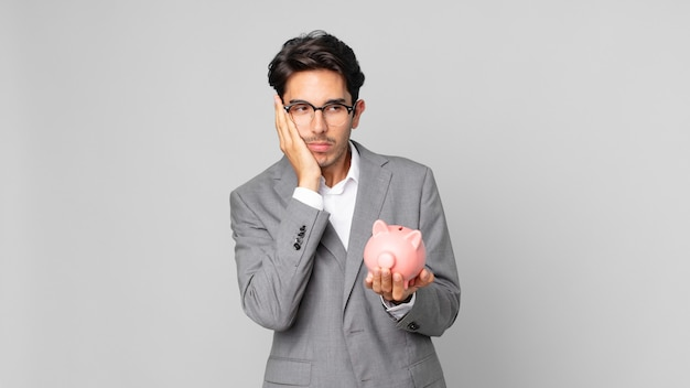 Young hispanic man feeling bored, frustrated and sleepy after a tiresome and holding a piggy bank