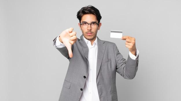 젊은 히스패닉 남자가 십자가를 느끼고 신용 카드를 들고 엄지손가락을 아래로 보여줍니다.