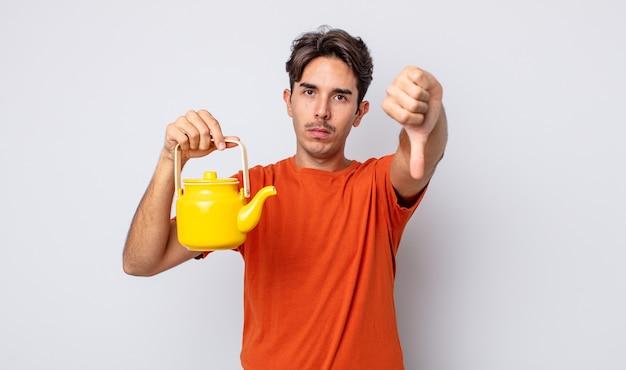 Молодой латиноамериканец чувствует крест, показывает палец вниз. концепция чайника