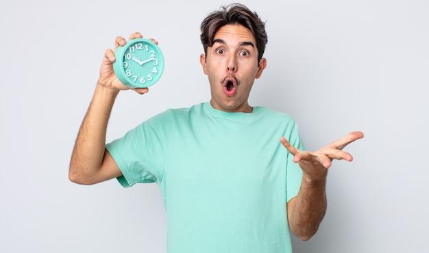 非常にショックを受け、驚いた若いヒスパニック系の男性。目覚まし時計の概念