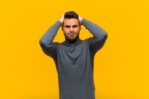 Young hispanic man feeling frustrated and annoyed, sick and tired of failure, fed-up with dull, boring tasks against orange wall