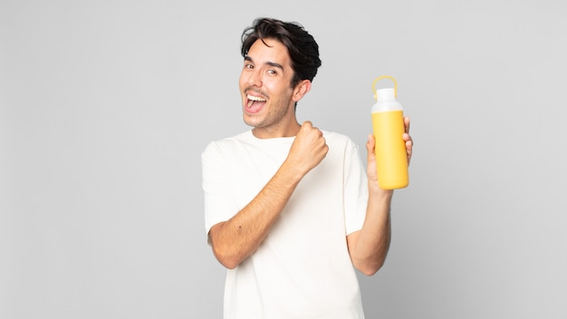 幸せを感じ、挑戦に直面している、またはコーヒー魔法瓶で祝っている若いヒスパニック系男性