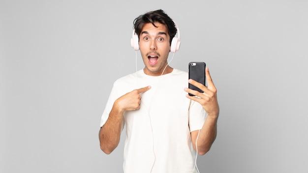 젊은 히스패닉 남자는 행복하고 헤드폰과 스마트폰으로 흥분하여 자신을 가리키고 있습니다.