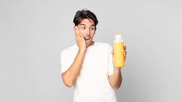 コーヒーの魔法瓶で幸せ、興奮、驚きを感じている若いヒスパニック系男性