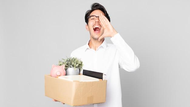 口の横に手を置いて大きな叫び声をあげて、幸せを感じている若いヒスパニック系の男性。解雇の概念