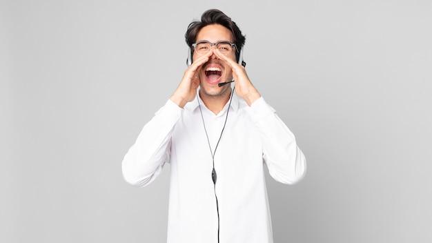 口の横に手を置いて大きな叫び声をあげて、幸せを感じている若いヒスパニック系の男性。テレマーケティングの概念