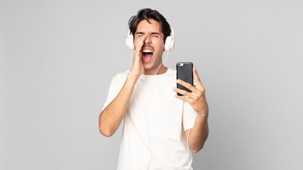 ヘッドフォンとスマートフォンで口の横にある手で大きな叫び声をあげて、幸せを感じている若いヒスパニック系男性