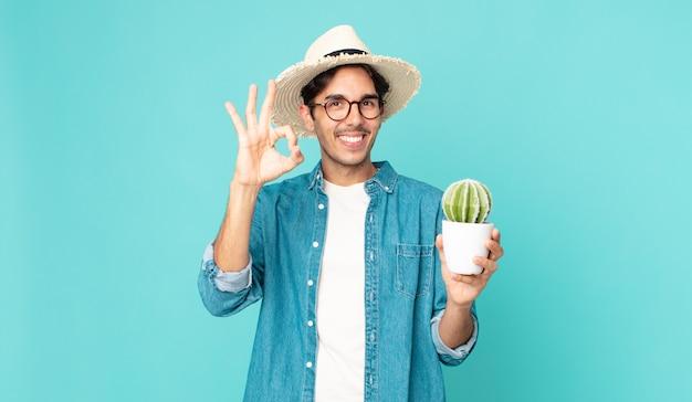 幸せを感じ、大丈夫なジェスチャーで承認を示し、サボテンを保持している若いヒスパニック系男性