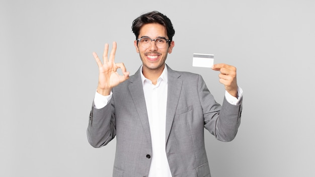 Young hispanic man feeling happy, showing approval with okay gesture and holding a credit card