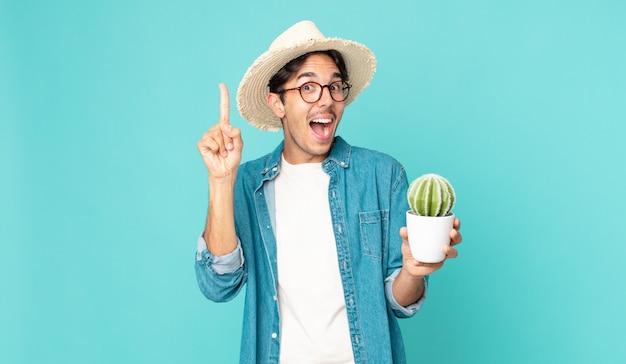 アイデアを実現し、サボテンを持った後、幸せで興奮した天才のように感じる若いヒスパニック系の男性