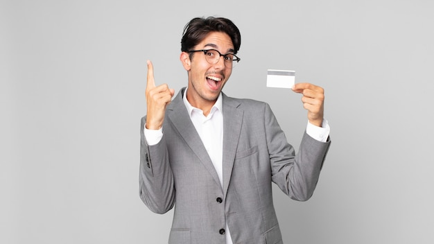 Young hispanic man feeling like a happy and excited genius after realizing an idea and holding a credit card