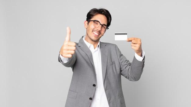 젊은 히스패닉 남자는 자랑스러워하며 엄지손가락을 치켜들고 긍정적으로 웃고 신용 카드를 들고 있습니다.