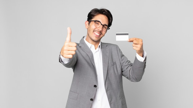 Young hispanic man feeling proud,smiling positively with thumbs up and holding a credit card
