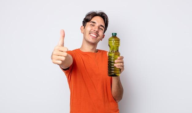 Молодой латиноамериканец чувствует себя гордым, позитивно улыбаясь, подняв палец вверх. концепция оливкового масла