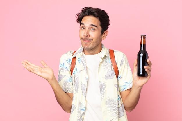젊은 히스패닉 남자는 어리둥절하고 혼란스럽고 의심하며 맥주 한 병을 들고 있습니다.