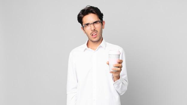 困惑と混乱を感じ、テイクアウトのコーヒーを持っている若いヒスパニック系男性