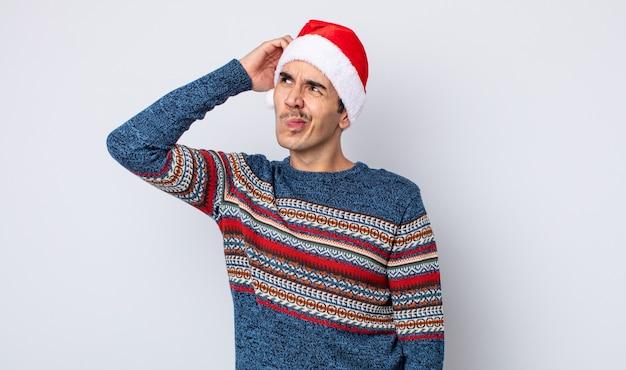 若いヒスパニック系の男性は、頭をかいて、戸惑い、混乱していると感じています。新年とクリスマスのコンセプト