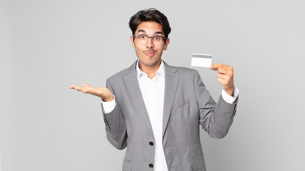 Young hispanic man feeling puzzled and confused and doubting and holding a credit card